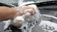 close up of hand washing a car with a soapy sponge