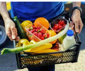 community volunteer carrying basket of fresh fruit and vegetables