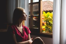 lady looking calm with her eyes closed by an open window