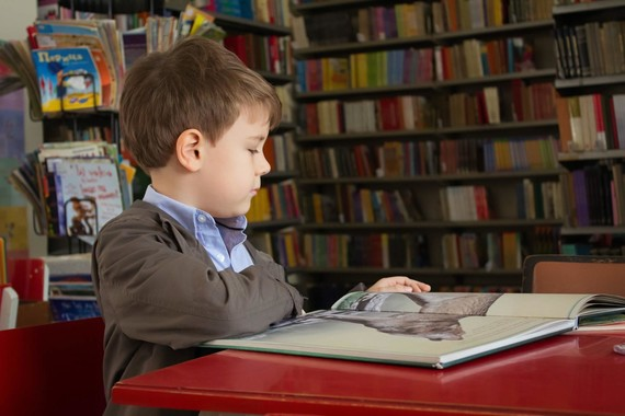 boy reading a book in a library