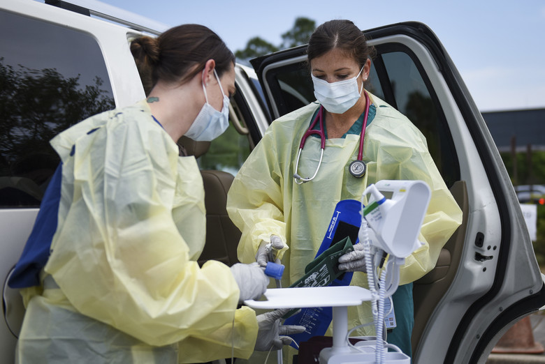 nurses in PPE at a drive through testing facility