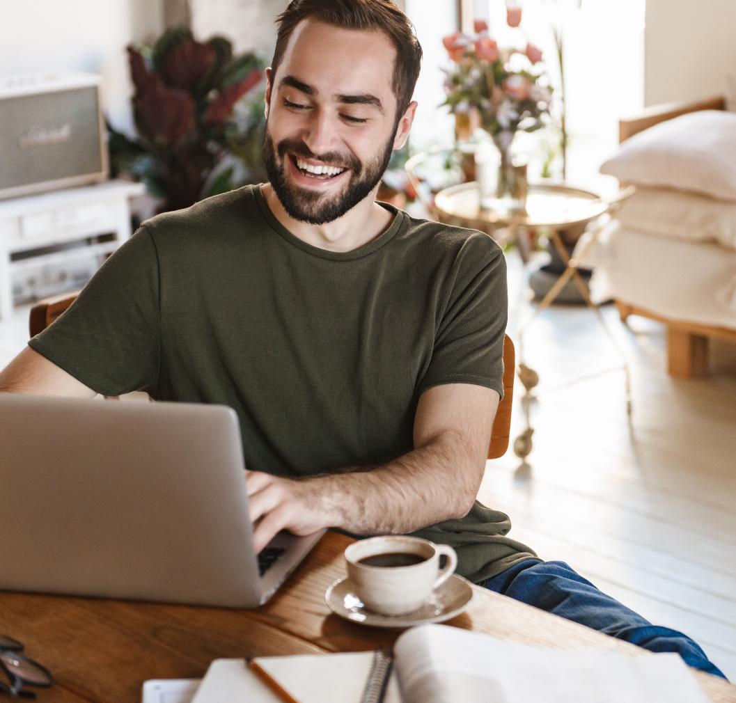 Man sat at laptop looking happy at home