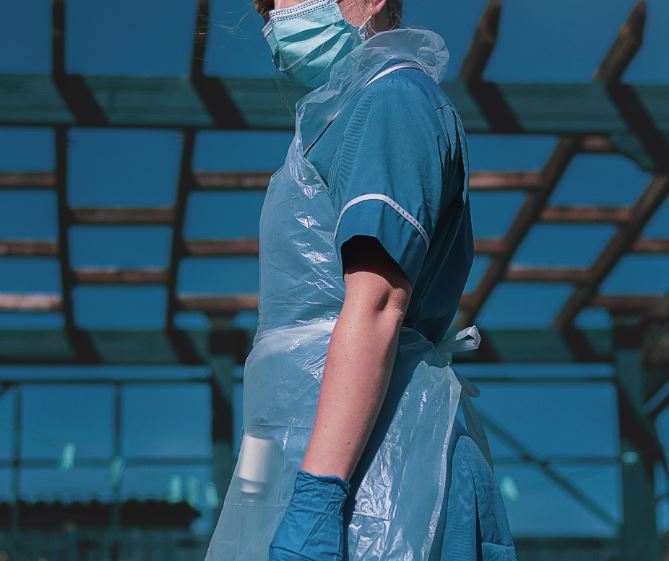 Carer wearing PPE facemask, apron and gloves