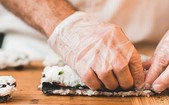 Close up of chef's hands preparing sushi