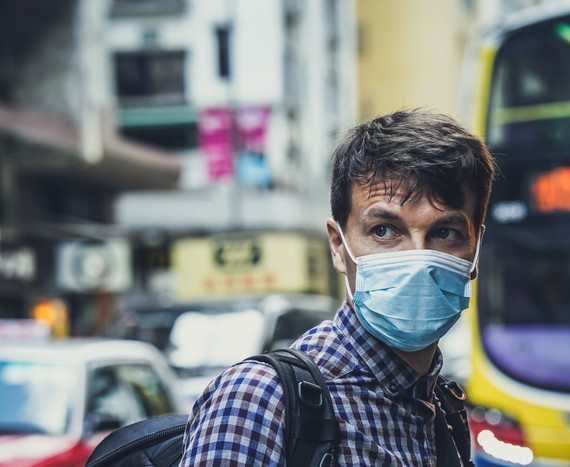 Man stood by a bus wearing a face mask
