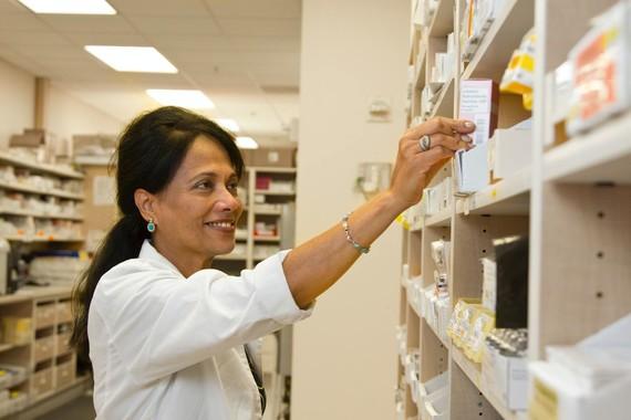 pharmacist reaching for medicine on a shelf