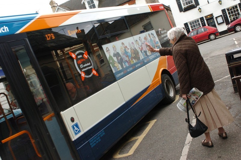elderly lady waving at bus