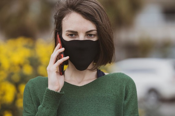 lady wearing a face mask on the phone