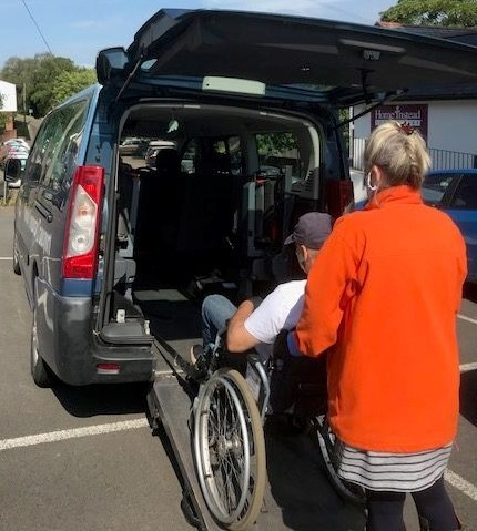 man in a wheelchair being helped into a car