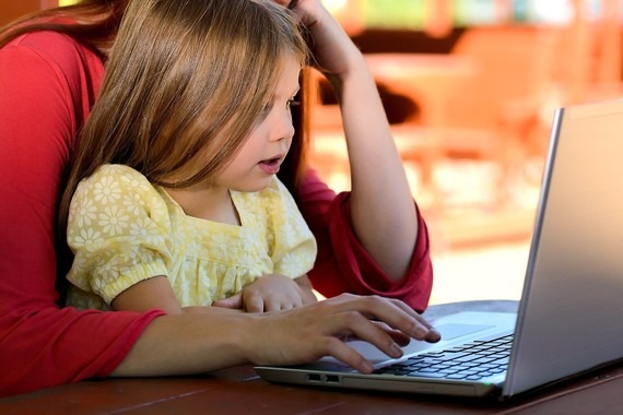 young girl sat at a laptop with her mother