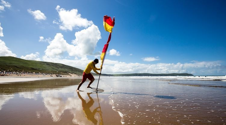RNLI lifeguard putting flag on a beach - Credit RNLI/Nathan Williams