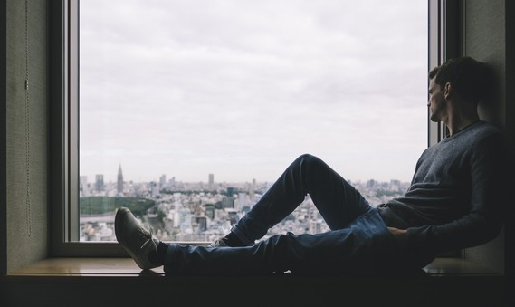 young man sitting in window looking alone
