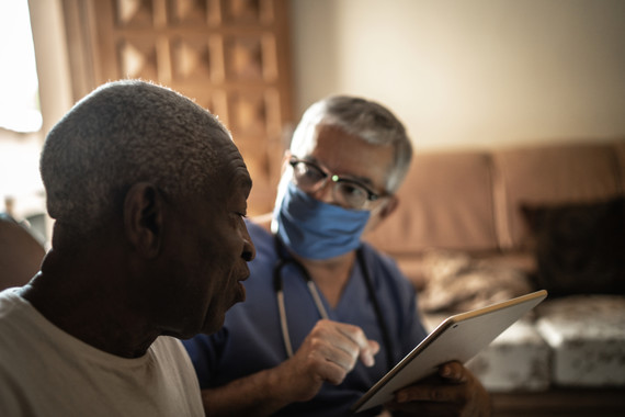 medical professional in a mask talking to a patient