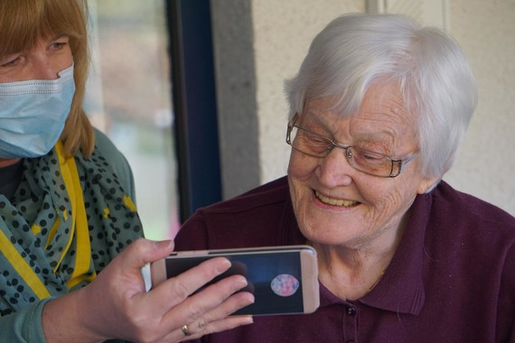 Elderly lady smiling at a picture on a phone with carer in mask stood next to her