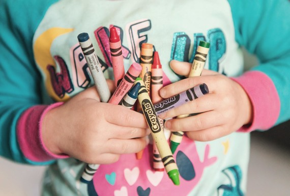 young child holding crayons