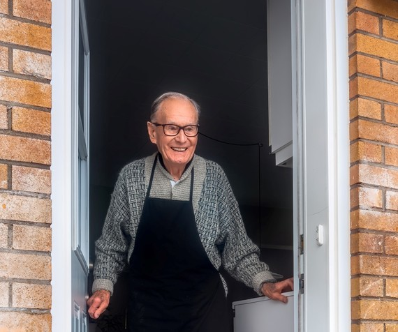 elderly man stood at door smiling
