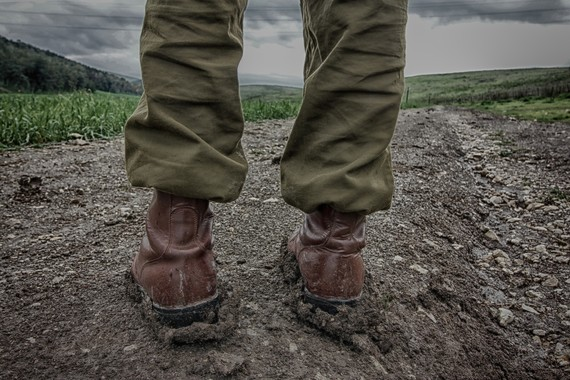 A person wearing muddy boots stood in a field