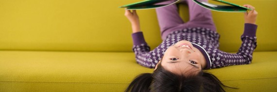 Child with a book upside down on a yellow sofa
