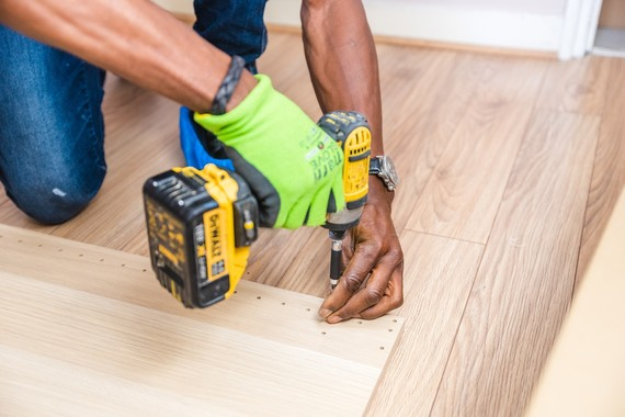 Tradesman using a drill on a wooden floor