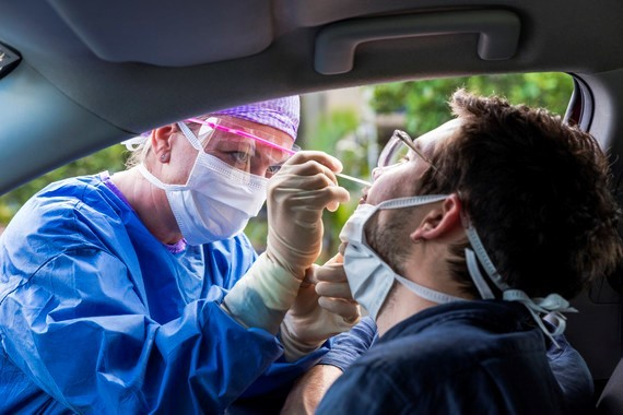 Man having a swab taken in his car by a health professional