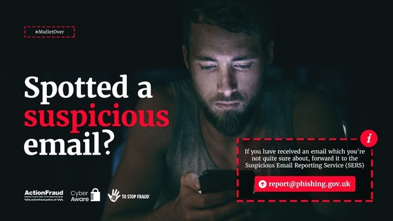 Man in the dark looking at his mobile phone with the words - Spotted a suspicious email?