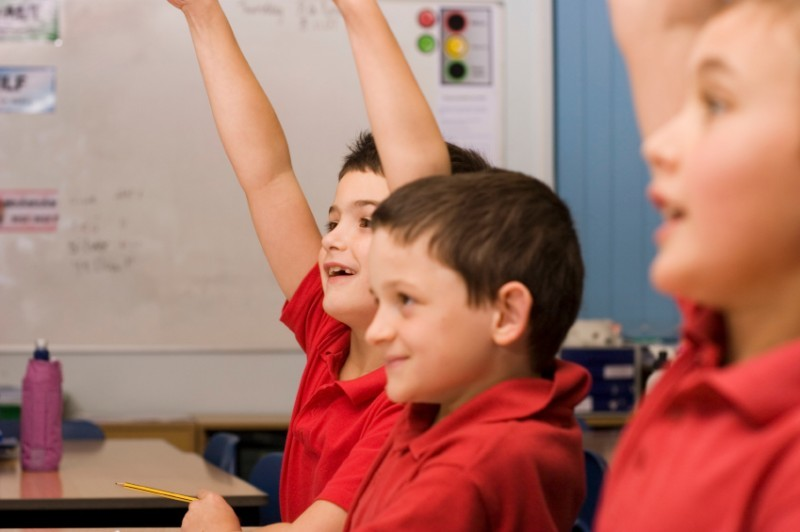 school children with hands up