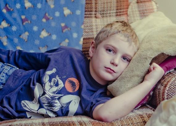 poorly boy lying on sofa