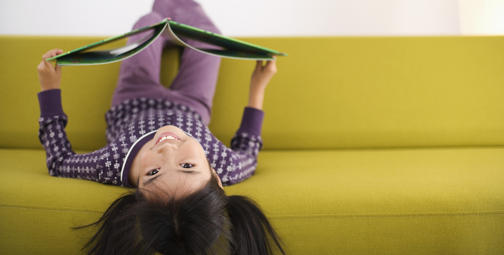 girl hanging upside down off a sofa with a book