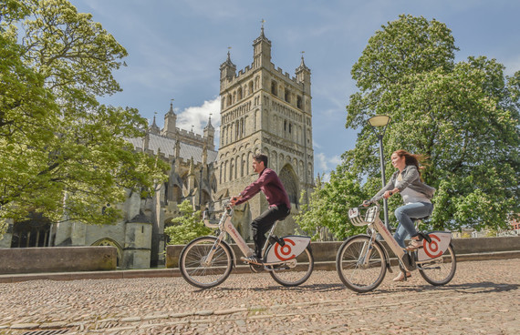 Young people cycling past Exeter cathedral