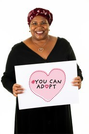 Jenny holding up a sign saying 'you can adopt'