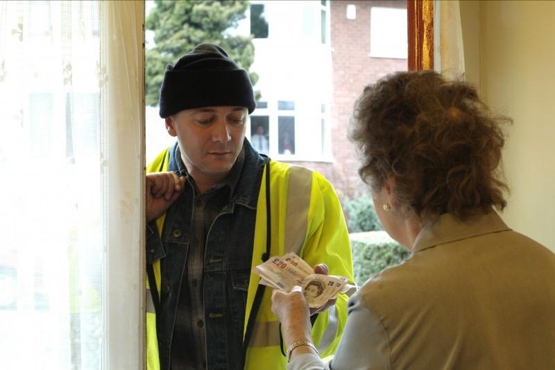 Man at doorstep with older woman handing over cash