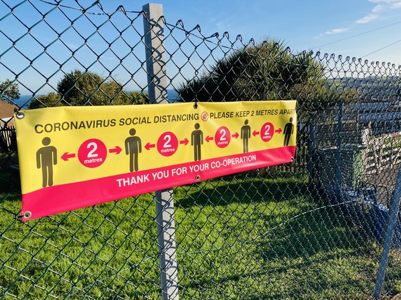 social distancing sign on school fence