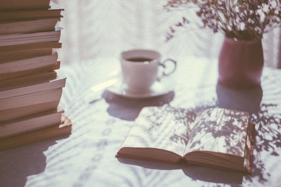 An open book on a table with a cup of tea next to it