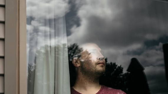 man inside looking out of window