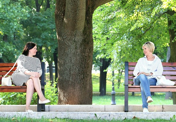 two women meeting sat on benches