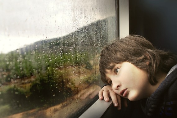 sad child looking out of rainy window