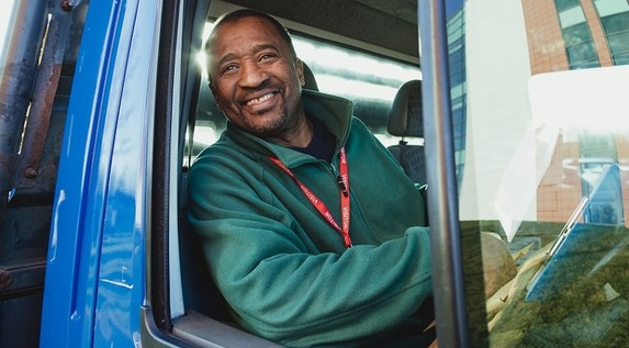 Man in the cab of a lorry, smiling at the camera