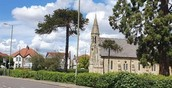 An image of a church with trees and hedges