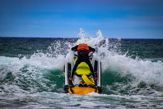RNLI lifeguard punching through surf on a rescue water craft