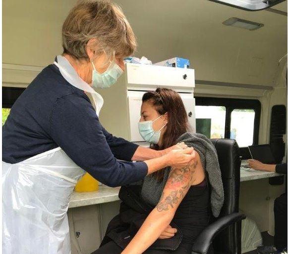 A woman receiving her vaccine in a mobile van
