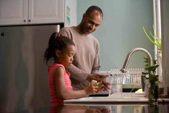 Father washing hands with daughter
