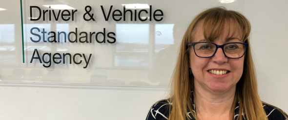 """Marian Kitson standing in front of a sign reading """"Driver and Vehicle Standards Agency"""""""