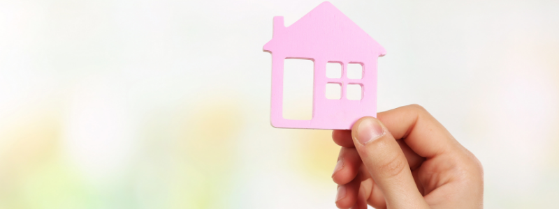 Hand holding a small wooden house against a coloured background