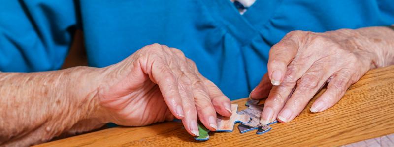 Elderly lady completing a jigsaw