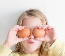 A young girl holding two eggs