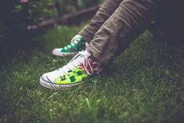 a young person is sitting outside on a lawn, the photo shows their legs and colourful trainers