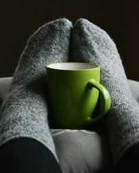 a pair of feet in warm, grey woollen socks rest on a cushion with a green mug propped between them