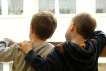 Two young boys looking out a window.