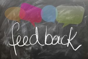 the word 'feedback' is written in white chalk on a slate board