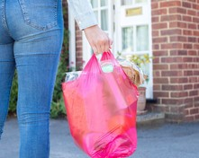 A woman holding a bag of shopping.